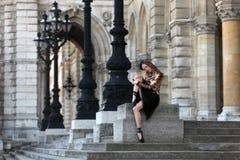 坐在宫殿前面的黑裙子的美丽的芭蕾舞女演员 免版税图库摄影