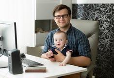 坐在家庭办公室和拿着他的1岁小儿子的微笑的年轻男性自由职业者画象  免版税库存图片