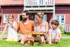 坐在家庭吃西瓜草前面的家庭  库存图片