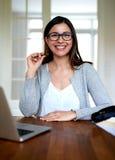坐在家挺直微笑的妇女办公桌 免版税库存图片