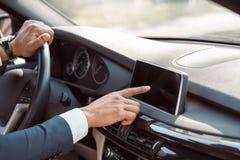 坐在导航员特写镜头的汽车改变的目的地里面的年轻商人司机 免版税库存照片