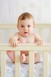 坐在小儿床的婴孩 库存照片