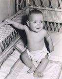 坐在小儿床的微笑的男婴 库存照片