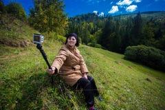 坐在小山顶部和享受山景的愉快的年长妇女 免版税库存照片