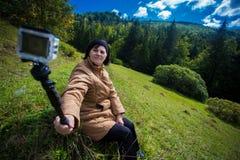 坐在小山顶部和享受山景的愉快的年长妇女 库存照片