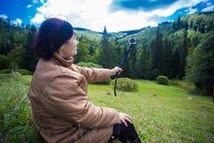 坐在小山顶部和享受山景的愉快的年长妇女 图库摄影