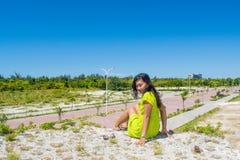 坐在小山顶部的年轻美丽的亚裔女孩画象面对照相机 免版税库存照片