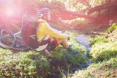 坐在小河附近和看自然的山骑自行车的人 库存照片