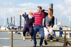 坐在小游艇船坞码头的朋友 库存照片