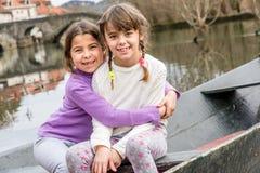 坐在小船和拥抱的两个姐妹 图库摄影