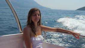 坐在小船和航行在海慢动作的年轻俏丽的妇女 4K 股票录像