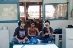 坐在小船的三个人在码头 免版税图库摄影