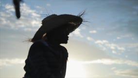 坐在小船的年轻非洲人画象  在草帽的男性去钓鱼的海 股票视频