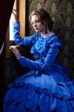 坐在小轿车的蓝色葡萄酒礼服的少妇在胜利附近 免版税库存图片