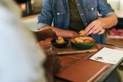 坐在小餐馆的两个人制表分享可口食物 免版税库存照片