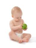 坐在尿布的愉快的儿童小小孩用绿色苹果 库存图片