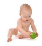 坐在尿布的愉快的儿童小小孩用绿色苹果 免版税库存照片