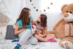 坐在屋子和笑里的两个微笑的姐妹 免版税库存照片