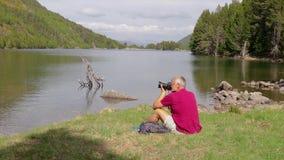 坐在山湖旁边的旅游人和拍照片 影视素材