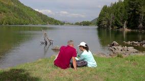 坐在山湖旁边的旅游夫妇和拍与手机的一张照片 股票视频
