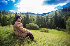 坐在山的小山顶部的愉快的年长妇女 库存照片