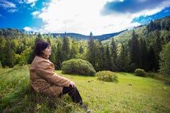 坐在山的小山顶部的愉快的年长妇女 库存图片