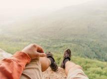坐在山的探险家 库存图片