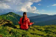 坐在山的瑜伽姿势的红色夹克的少妇 免版税库存图片