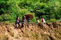 坐在山顶部的一个小组未认出的种族孩子 库存照片