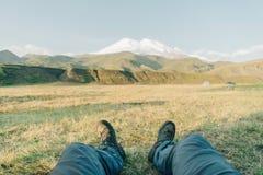 坐在山Elbrus前面的人 图库摄影