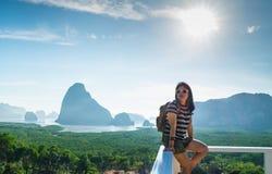 坐在山panora的愉快的年轻旅客妇女背包徒步旅行者 库存图片
