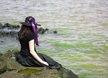 坐在岩石的女孩在海岸 免版税库存照片