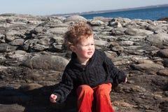 坐在岩石附近的年轻男孩在海洋 库存照片