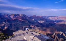 坐在岩石露头边缘的远足者有大峡谷的全景 免版税库存图片
