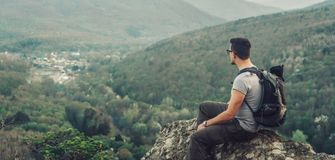 坐在岩石顶部的男性旅客 免版税图库摄影