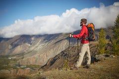 坐在峡谷边缘的英俊的年轻有胡子的男性远足者看  库存图片