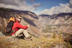 坐在峡谷边缘的英俊的年轻男性远足者看  库存图片