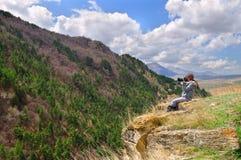 坐在峭壁边缘和为山风景照相的女孩 免版税库存照片