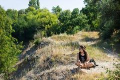 坐在峭壁边缘的女孩 库存照片