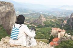 坐在峭壁边缘的妇女withTibetan狗狗俯视迈泰奥拉谷 免版税图库摄影