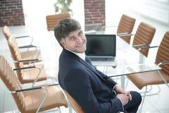 坐在工作书桌的微笑的经理在会议室 库存照片