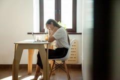 坐在工作地点的疲乏的困女实业家 库存照片
