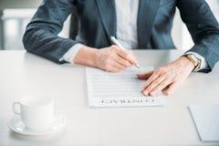坐在工作场所和签署的合同的女实业家 库存图片