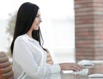 坐在工作场所的成功的年轻女商人 免版税库存照片