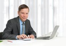 坐在工作场所的生意人 免版税库存照片