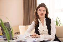 坐在工作场所的年轻俏丽的女实业家在办公室 免版税库存照片