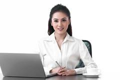 坐在工作表里的一个亚裔女商人 免版税图库摄影