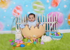 坐在巨人复活节彩蛋的可爱的非洲婴孩 免版税库存照片