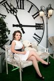 坐在巨大的时钟附近的女孩 免版税图库摄影