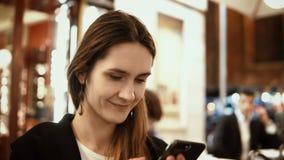 坐在市中心在晚上和使用智能手机的年轻美丽的妇女画象在咖啡馆 免版税库存照片